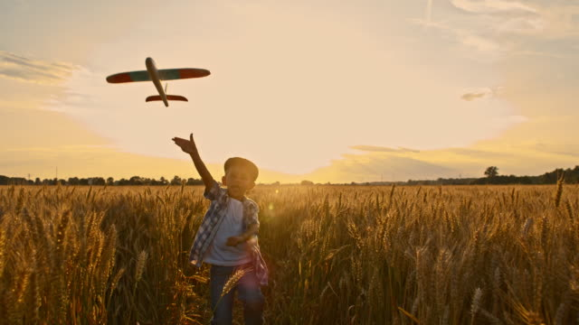 SLO MO Boy throwing an airplane Slow motion camera stabilization shot of a little boy throwing an airplane while running through a field of wheat. Also available in 4K resolution. wheat stock videos & royalty-free footage