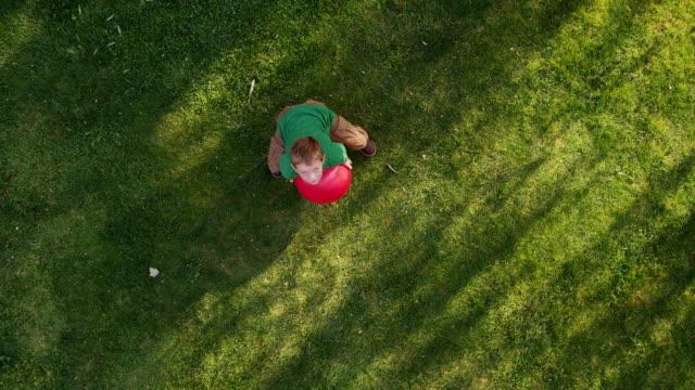 vidéos et rushes de garçon lancer ballon rouge, au-dessus de votre tête, tourné - balle ou ballon