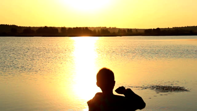boy throwing stones into the river at sunset, silhouette, sun glare on the water video