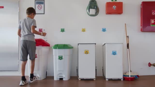 Boy throws a plastic bottle into the right trash can. Recycling plastic, proper sorting of garbage Boy throws a plastic bottle into the right trash can. Recycling plastic, proper sorting of garbage environmental consciousness stock videos & royalty-free footage
