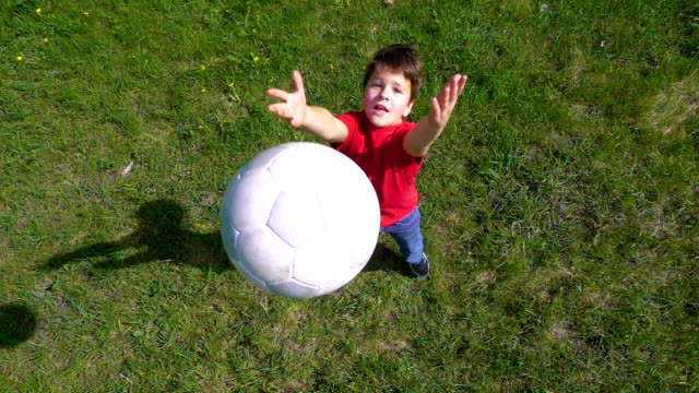 vídeos de stock e filmes b-roll de boy throws up the ball, standing on green field, slow motion - chutar