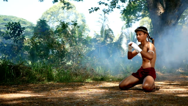 vídeos de stock e filmes b-roll de a boy training muay thai - boxe tailandês