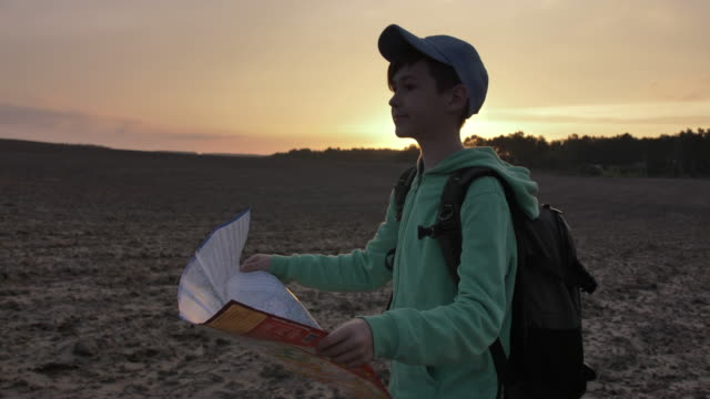 boy travel with a map at sunset outdoors, landmark