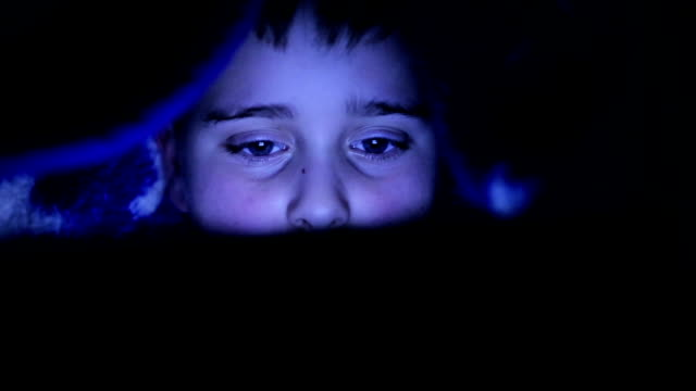Boy under cover using tablet video