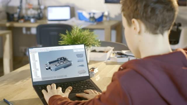 stockvideo's en b-roll-footage met jongen ontworpen de laptopcomputer gebruik te maken van 3d component in cad-programma voor zijn wetenschappelijke robotica-klasse. - estland