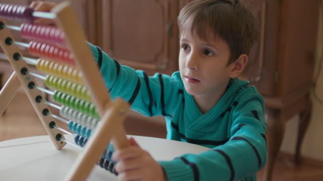 boy using abacus, slow motion - dedizione video stock e b–roll