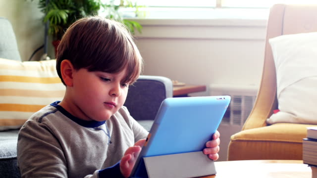 Boy using digital tablet in living room 4k video