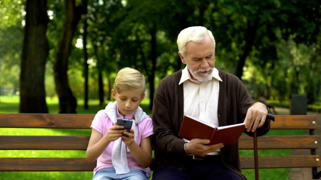 pojke med smartphone medan farfar läsebok, begreppet teknik vs papper - digital reading child bildbanksvideor och videomaterial från bakom kulisserna
