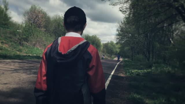 Boy walking alone in the park video