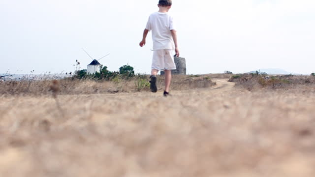 Boy walking on hilltop with windmills video