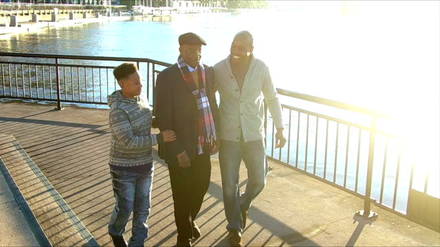 Boy walking with father and great grandfather A 10 year old African-American boy walking along a city waterfront with his father and great grandfather. The senior man is in his late 70s. He is walking slowly, with his family giving him support. support stock videos & royalty-free footage