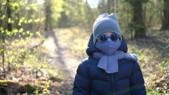vídeos y material grabado en eventos de stock de niño camina en una máscara protegida del virus y gafas redondas de colores - abrigo