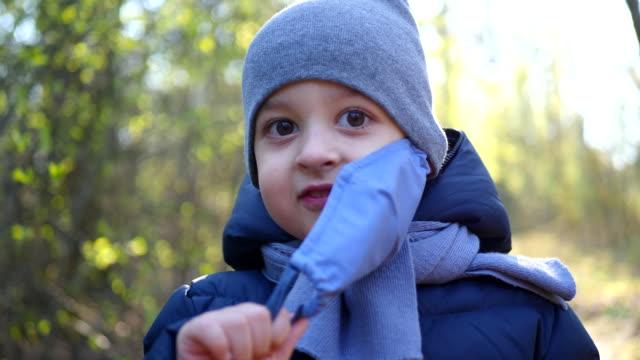 vídeos y material grabado en eventos de stock de niño camina en una máscara protegida del virus - abrigo