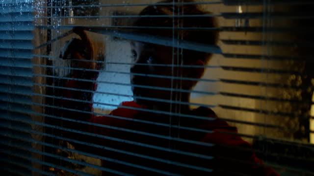 a boy watching rainstorm from room - burza filmów i materiałów b-roll