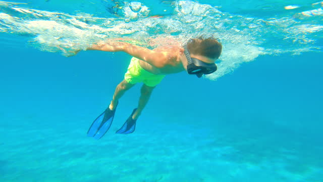 Boy wearing a diving mask and fins and swimming in the sea