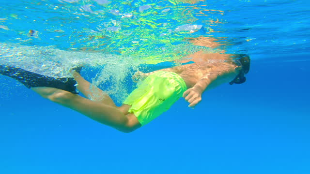 Boy wearing a diving mask and fins swimming underwater