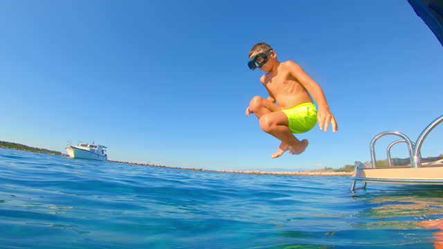 Boy wearing a diving mask jumping off the boat into the blue sea
