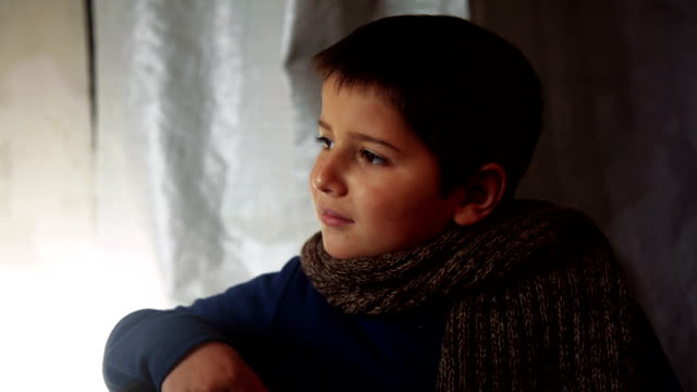 Boy wearing a scarf sitting and looking out the window video