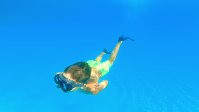 Boy wearing  diving mask and swimming in the blue sea on a sunny day