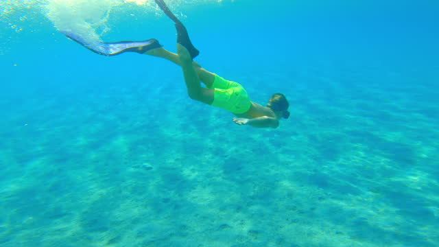 Boy wearing fins and swimming underwater