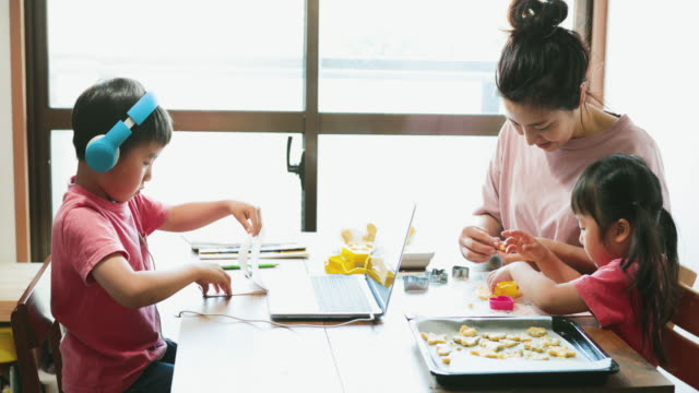 vídeos y material grabado en eventos de stock de niño que lleva auriculares tomando un curso de e-learning con la familia en la sala de estar - stay home
