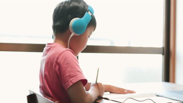vídeos de stock, filmes e b-roll de menino usando fone de ouvido fazendo um curso de e-learning com laptop - salas de aula