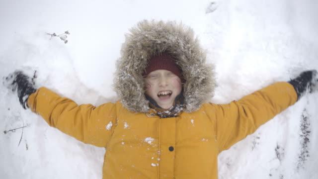 4K boy wearing yellow coat making snow angel lying on ground smiling
