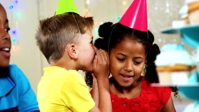 Boy whispering to girl while sitting with friends during birthday party 4k video