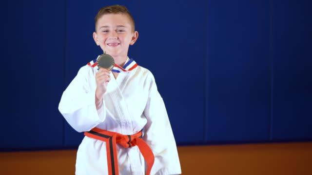 vídeos de stock, filmes e b-roll de garoto vence competição de taekwondo - artes marciais