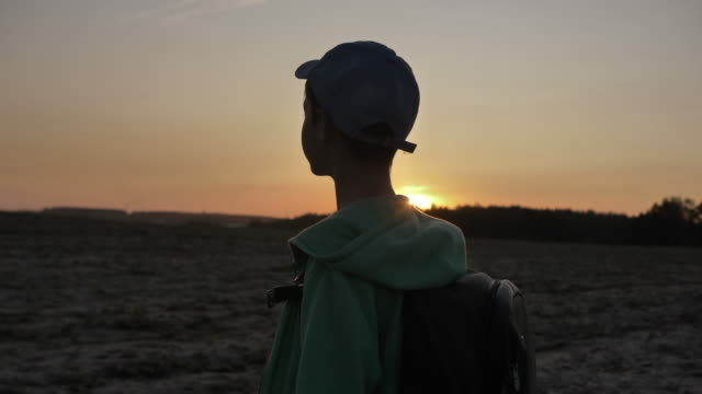 boy with a backpack goes at sunset on the plain outdoors, traveling video