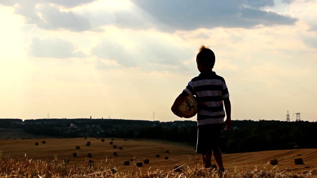 boy with a ball in a field at sunset, boy dreams of becoming a soccer player video