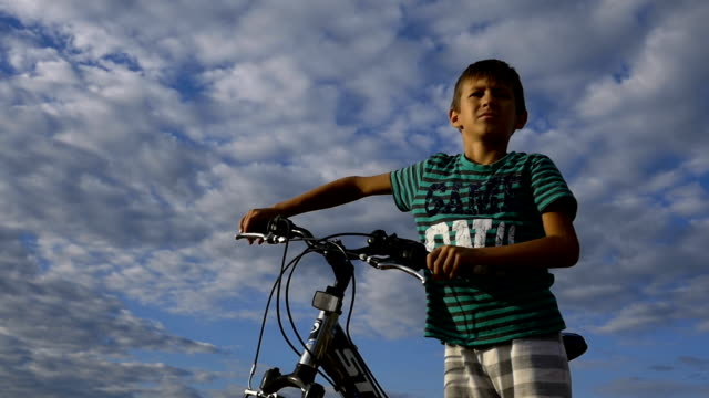 boy with a bicycle against the sky looking afar video