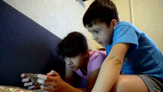 bir kız ile erkek bir akıllı telefon bakmak - dijital yerli stok videoları ve detay görüntü çekimi