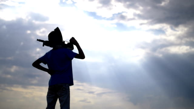 boy with a gun at sunset on the background of clouds, ak 47 video