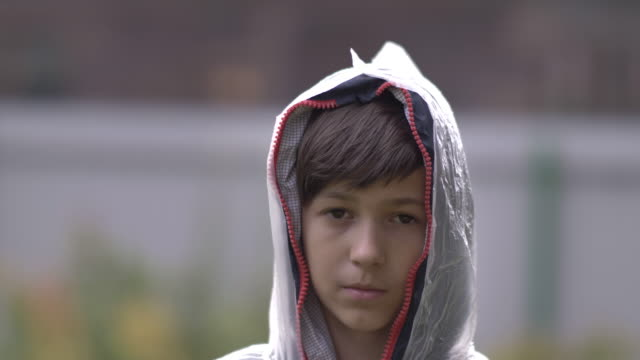 boy with a sad face is standing in a raincoat in the rain, pain on face video