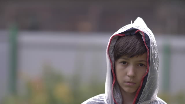 boy with a sad face is standing in a raincoat in the rain video