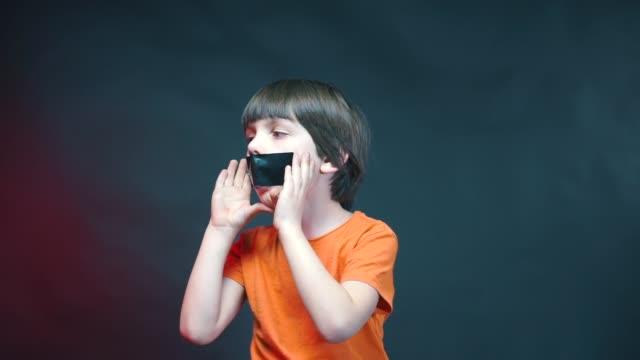 stockvideo's en b-roll-footage met een jongen met een verzegelde mond schreeuwt rond, een uitdrukking van kinderen protest. - kids online abuse