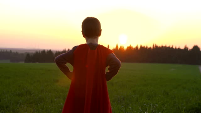 A boy with a superhero cape in a green field during sunset Slow motion shot of A boy with a superhero cape in a green field during sunset cape garment stock videos & royalty-free footage