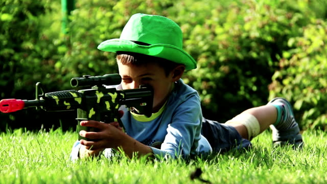 boy with a toy gun lying on the grass, takes aim video