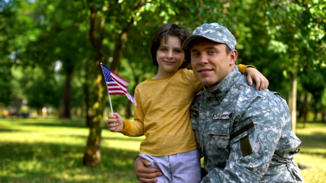 Boy with american flag hugging father military uniform, independence day, honor Boy with american flag hugging father military uniform, independence day, honor family 4th of july stock videos & royalty-free footage