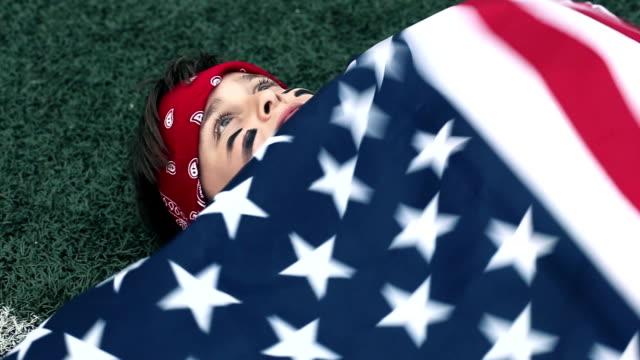 boy with an American flag thinking about winning video