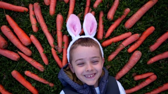 junge mit kaninchen-ohrkostüm legen in einem feld von karotten lächelnd - karotte peace stock-videos und b-roll-filmmaterial