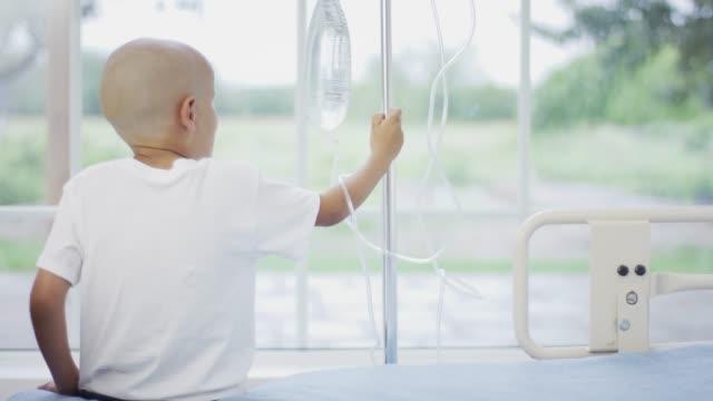 stockvideo's en b-roll-footage met jongen met kanker houden een iv infuus - kindertijd