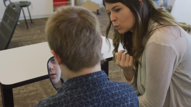 vídeos de stock, filmes e b-roll de garoto com síndrome de down usa um espelho durante uma sessão de fonoaudiologia - discurso