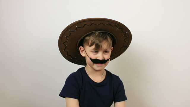 boy with false moustache and cowboy hat having fun. - april fools day stock videos and b-roll footage