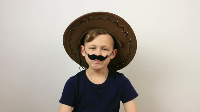 boy with false moustache and cowboy hat on grey background. - april fools day stock videos and b-roll footage