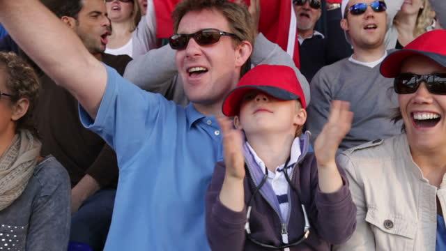 vidéos et rushes de garçon avec la famille dans la foule de spectateurs de sport - baseball