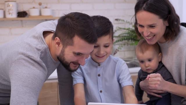 stockvideo's en b-roll-footage met jongen met familie speelspel op digitale tablet - vier personen