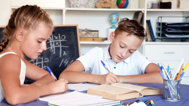 Boy with girl are writing in notebook their homework video