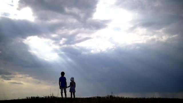 pojke med tjej hålla händerna mot bakgrund av vackra moln på kvällen - gå tillsammans bildbanksvideor och videomaterial från bakom kulisserna